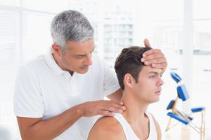 Chiropractor performing a physical exam on a patient that has back and neck pain due to chronic tight muscles and playing golf.