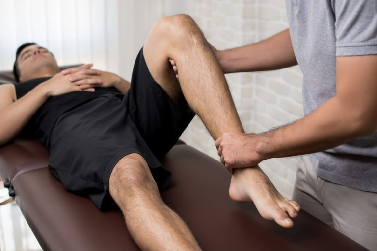 Man lying on back receiving treatment on his leg from therapist